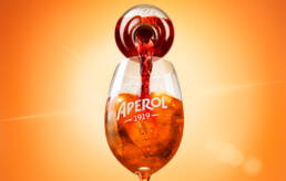 Aperol aperitif pouring into glass with ice with sun flare