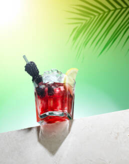 Bramble cocktail balancing on stone ledge with palm shadow