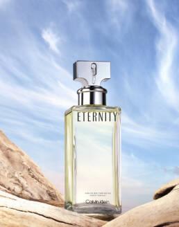 Calvin klein eternity fragrance perfume on driftwood with atmospheric sky