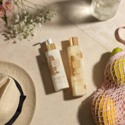 guava and gold body lotion and bath & shower gel on stone slabs with shopping net, papayas, straw hat and flowers