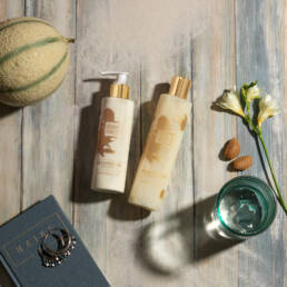 Guava and gold body lotion and bath & shower gel on wooden deck with sand, melon, water and book