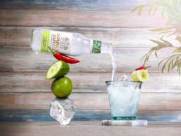 Double Dutch Drinks cucumber Marguerite bottle balancing on fruit stack poring into glass