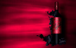 Diablo Valle Del Maure red wine dissolving into black ink on red background