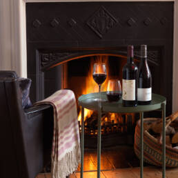New Hall and Bolney red wines on table in front of fireplace
