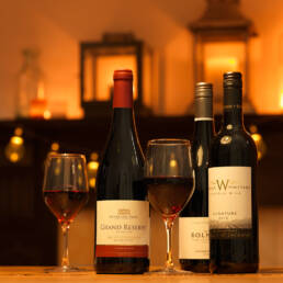 Stanlake Park, Bolney and Winbirri red wines on dining table in front of mantelpiece