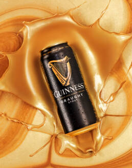 Guinness Draught Stout Can Splashing into Gold Liquid