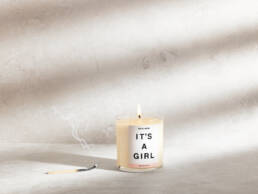 Scented candle with smoking match stick on stone background