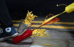 Ketchup and mustard squirting on pavement as Converse trainer steps on bottle