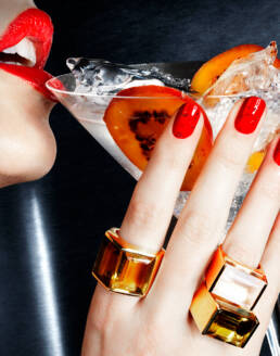 Model drinking from martini glass wearing oversized cocktail rings