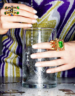 70s retro cocktail mixing glass and bar spoon with female hands wearing oversized cocktail rings