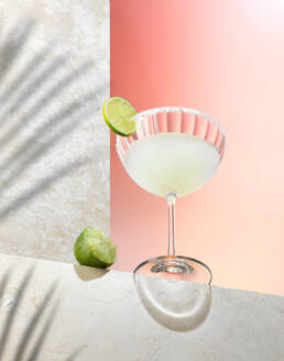 Tequila marguerita cocktail on stone set with limes and foliage shadows