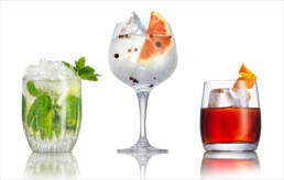 Mojito, gin and tonic & negroni classic cocktails on white background with reflection