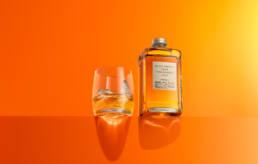 Nikka from the barrel Japanese whisky with tumbler on ledge in orange set