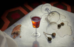 Aperitif cocktail on marble table with bread, olives and caper berries