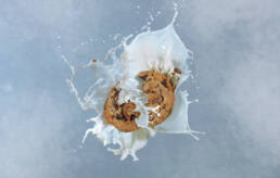 Chocolate chip cookie photographed breaking up into bits on impact with milk