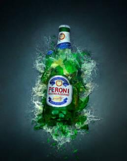 Peroni Nastro Azzurro beer bottle shattering on impact with floor
