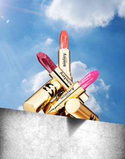Three golden Sisley lipsticks balancing on concrete ledge with blue sky and cloudy background with sun flare