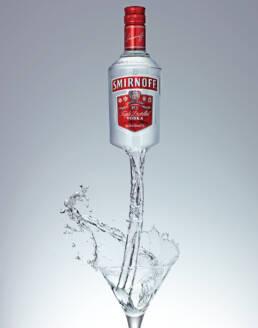 Smirnoff Vodka bottle melting into martini glass creating graphic splash