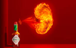 Tabasco Pepper Sauce in red architectural set spraying fireball from bottle cap