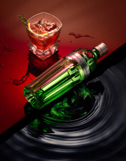 Tanqueray No Ten Gin bottle with negroni cocktail and water reflection and distortion