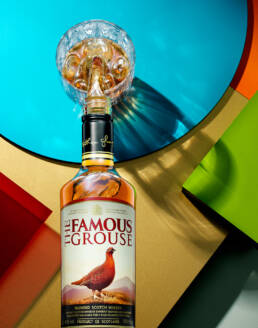 The Famous Grouse Blended Scotch Whisky Poured into Glass with ice in Graphic 70s setting